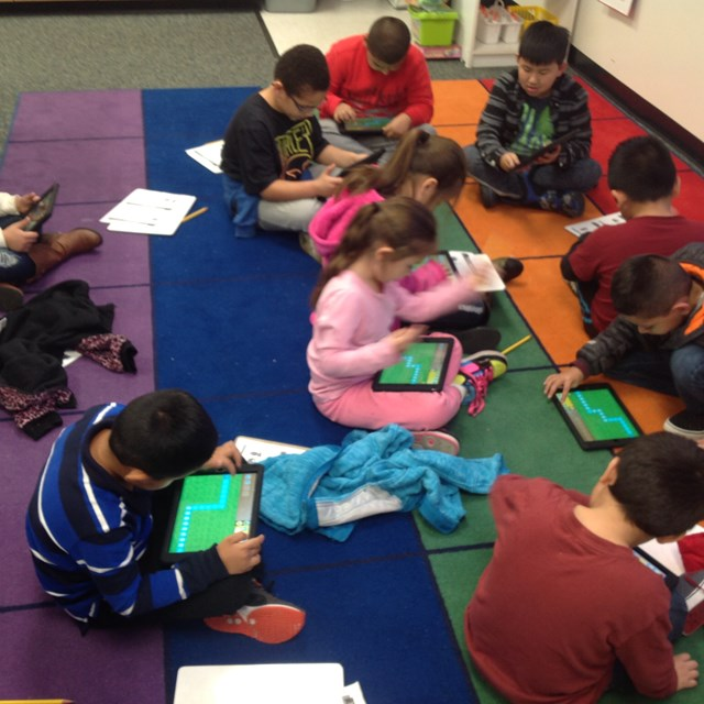 Students use tablets to practice computer coding.
