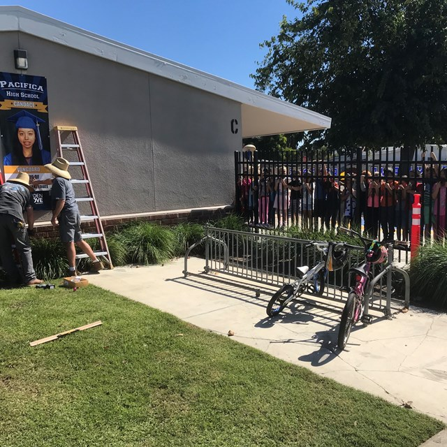 Scott and John from structural Maintenance Dept install college banners to the delight of our college bound Kinder students... who were writing about tools!